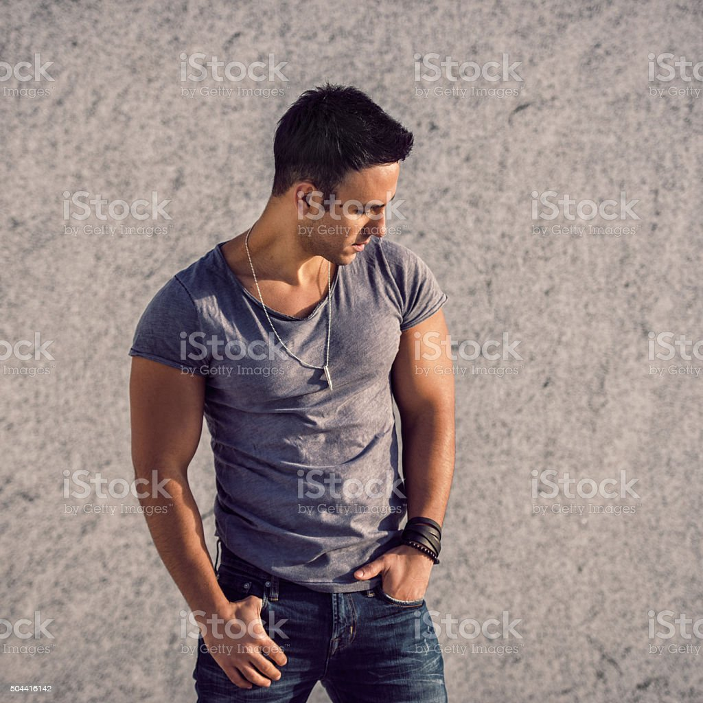 fashion model man wearing t-shirt and jeans posing near wall stock photo