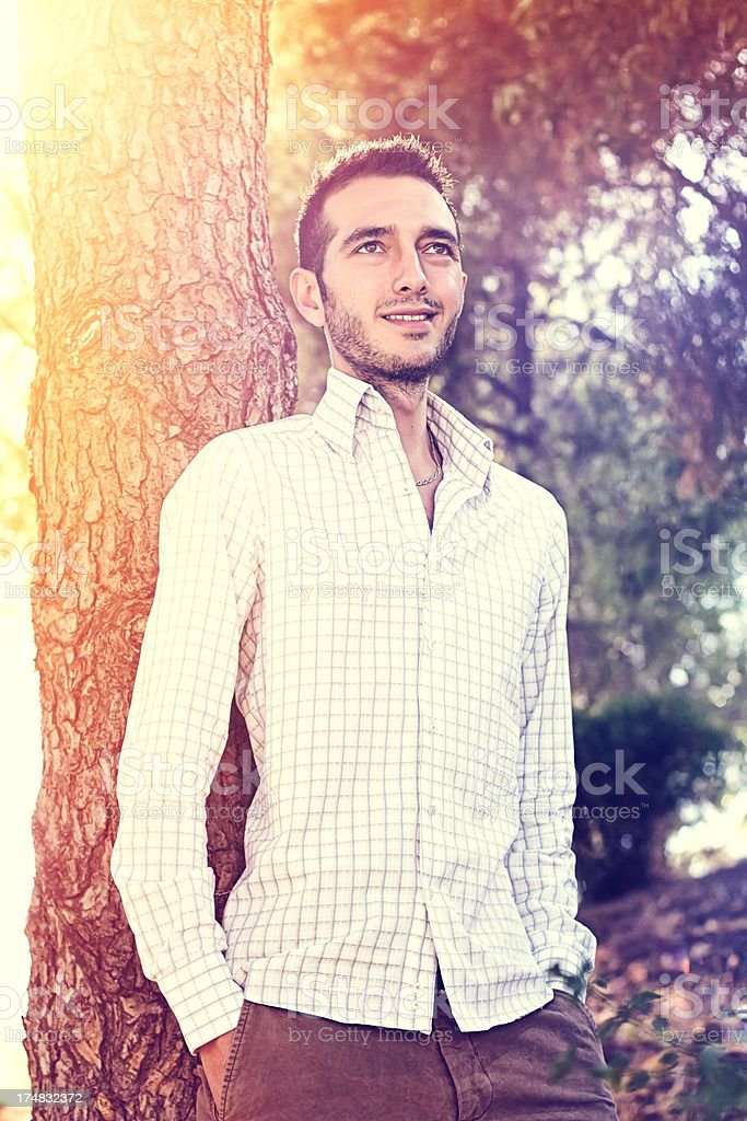 Fashion model posing leaning against a tree royalty-free stock photo