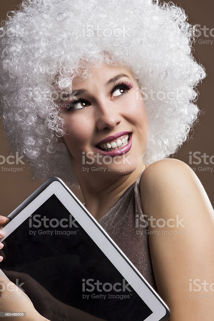 Fashion model with afro wig holding digital tablet royalty-free stock photo