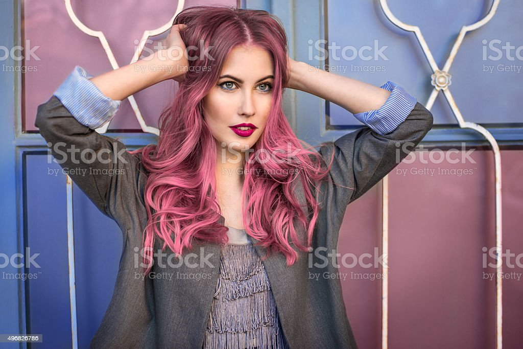 fashion model with curly pink hair posing near colorful wall stock photo