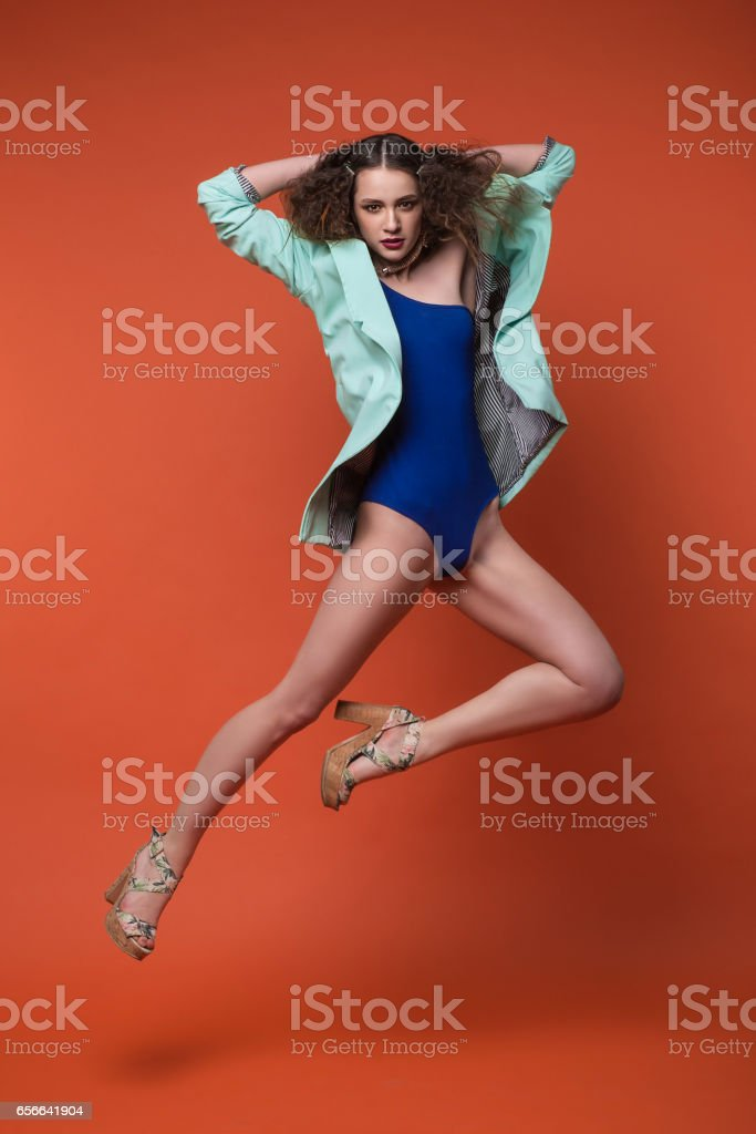Fashion photo of beautiful girl in studio. Young brunette woman in blue underwear and turquoise jacket posing on red background. Curly hairstyle. She is jumping and dancing. stock photo