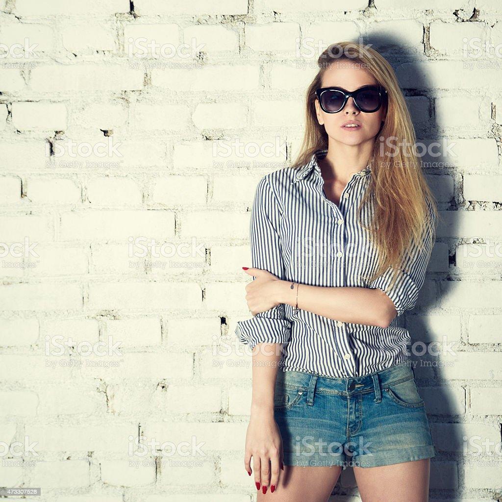 Fashion Photo of Hipster Woman at Brick Wall stock photo