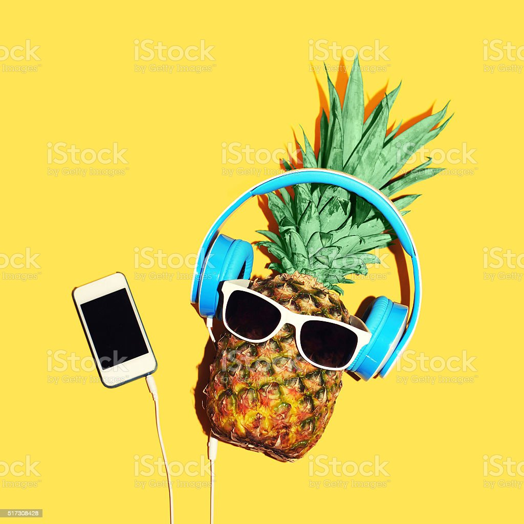 Fashion pineapple with sunglasses and headphones listens music on smartphone stock photo