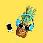 Fashion pineapple with sunglasses and headphones listens music on smartphone