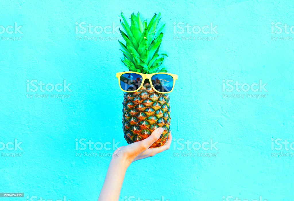 Fashion pineapple with sunglasses on blue background, hand holding...