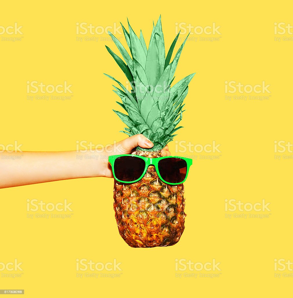 Fashion pineapple with sunglasses on yellow background, hand holding ananas stock photo