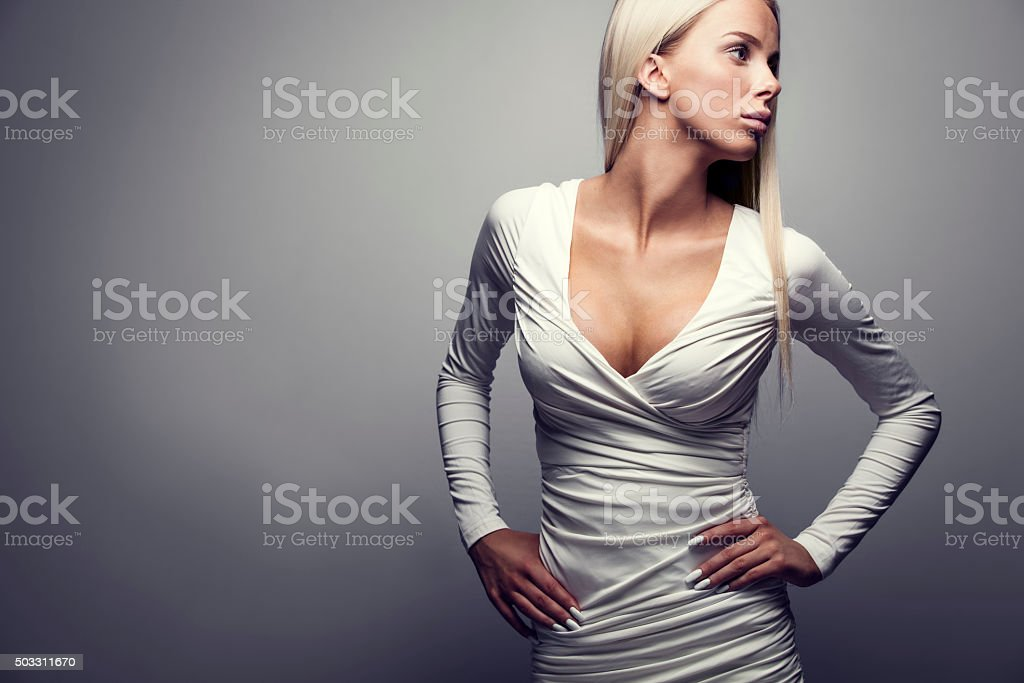 Fashion portrait of a blonde woman in white dress stock photo