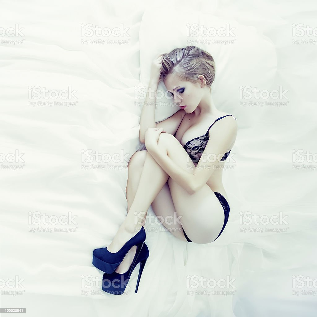 Fashion portrait of a sensual girl in white bed royalty-free stock photo