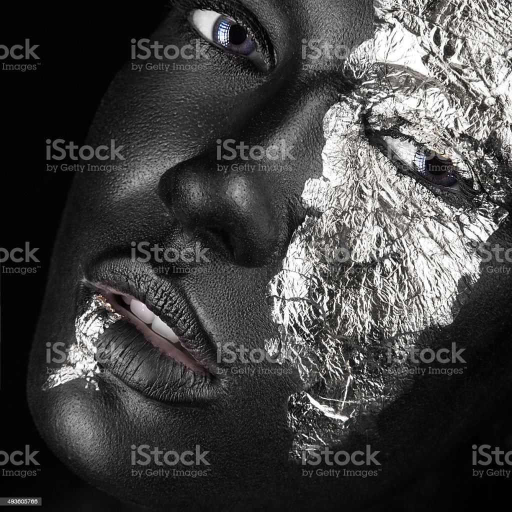 fashion portrait of dark-skinned girl with silver foil make-up. stock photo