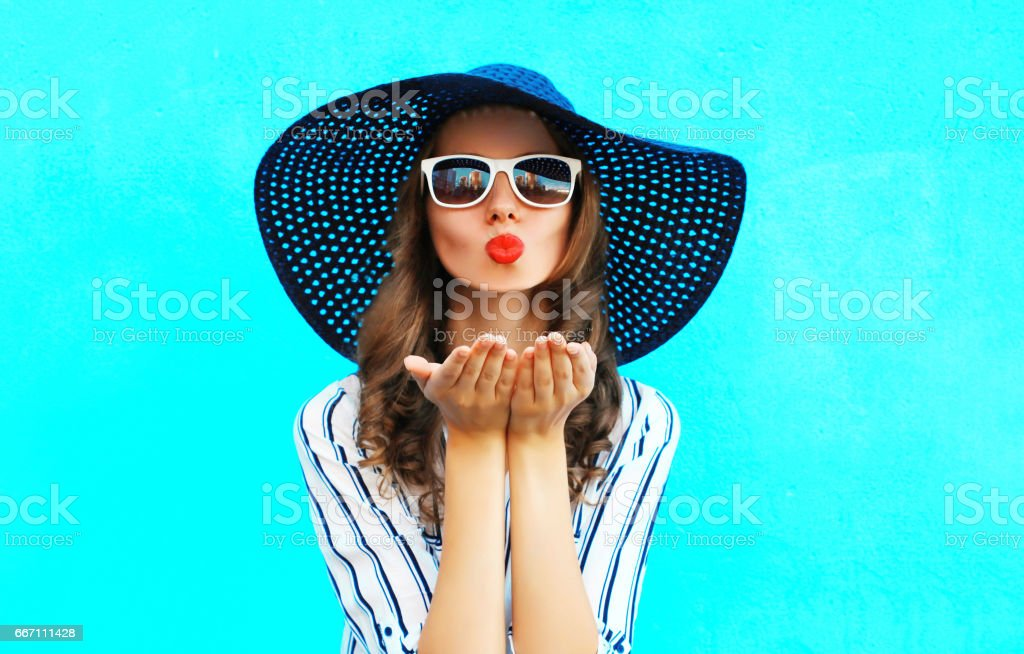 Fashion portrait pretty woman with red lips is sends an air kiss in straw summer hat over colorful blue background stock photo