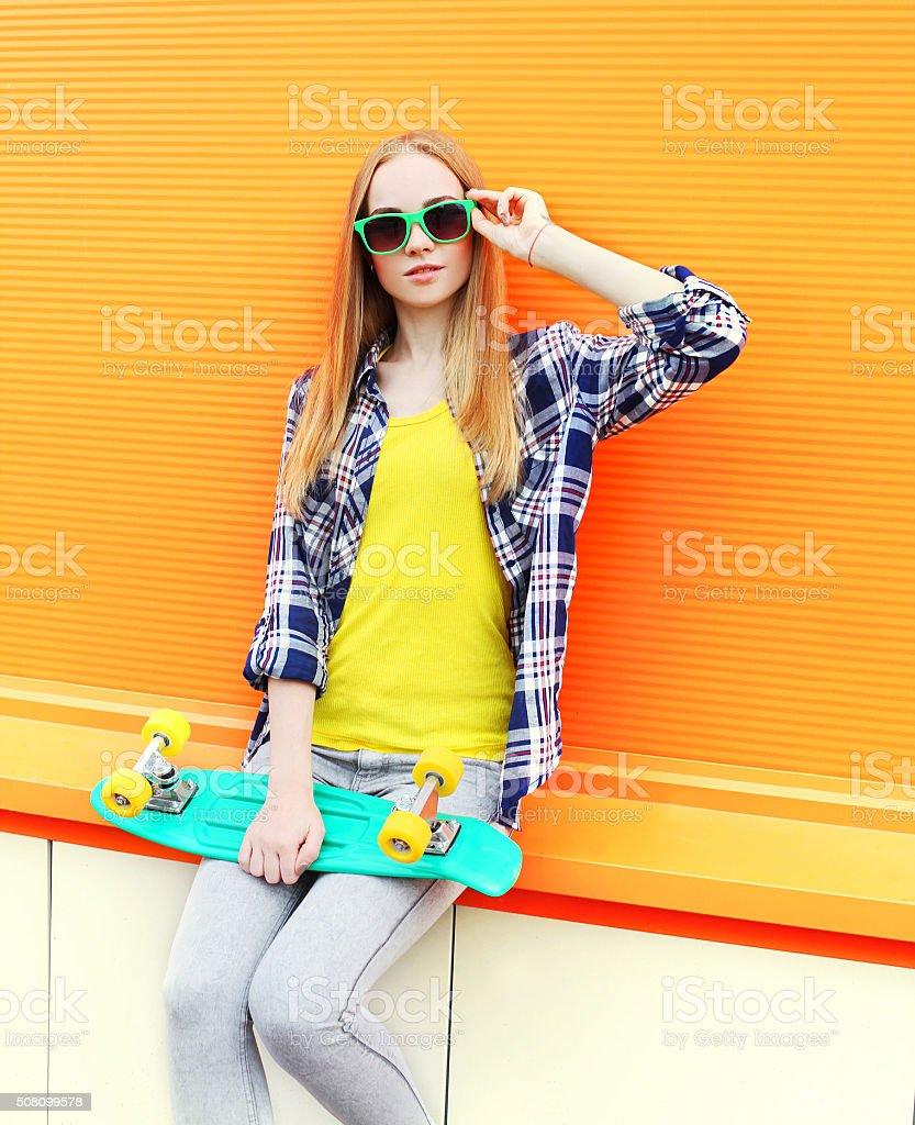 Fashion pretty blonde girl wearing a sunglasses with skateboard stock photo