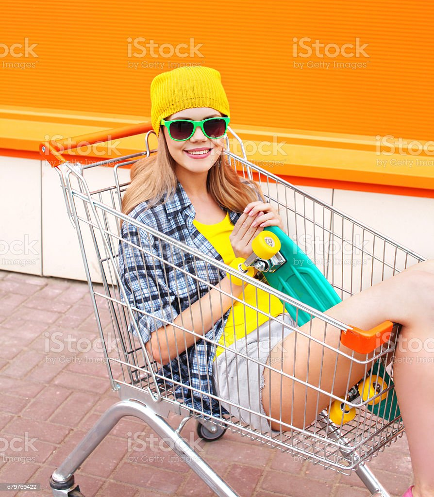 Fashion pretty cool girl in trolley cart with skateboard stock photo