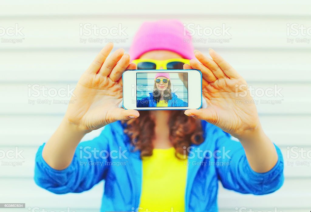 Fashion pretty cool girl taking photo self portrait on smartphone stock photo
