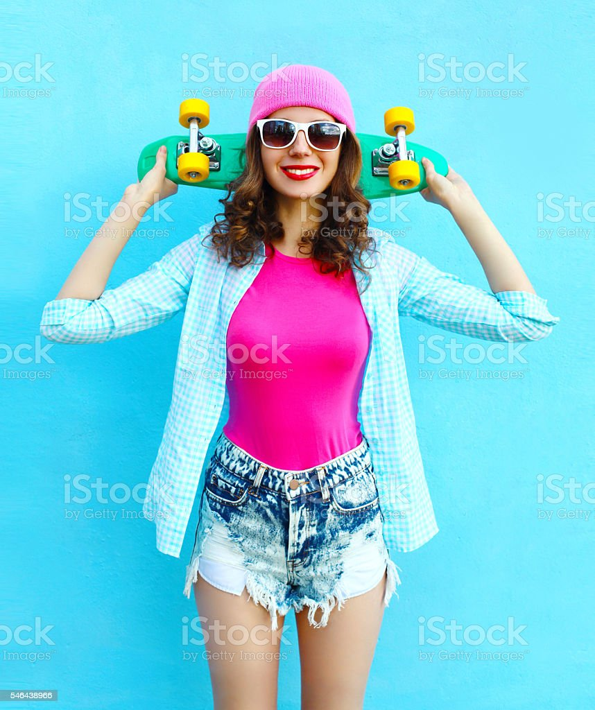 Fashion pretty cool woman in pink style with skateboard stock photo