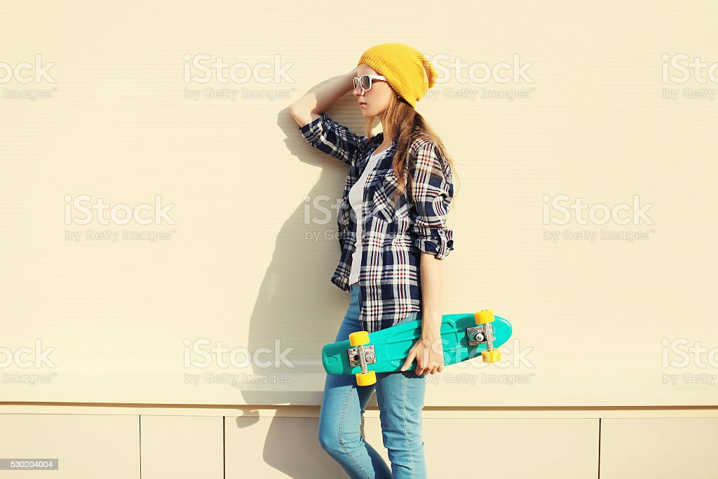 Fashion pretty girl wearing a colorful clothes with skateboard stock photo