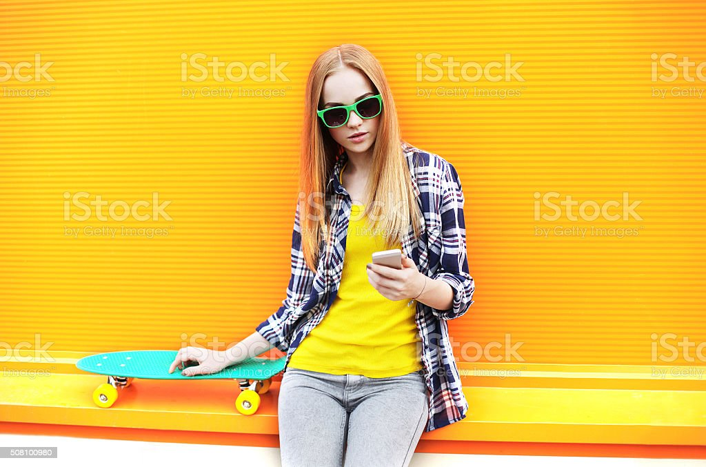 Fashion pretty girl with skateboard using smartphone over colorful stock photo