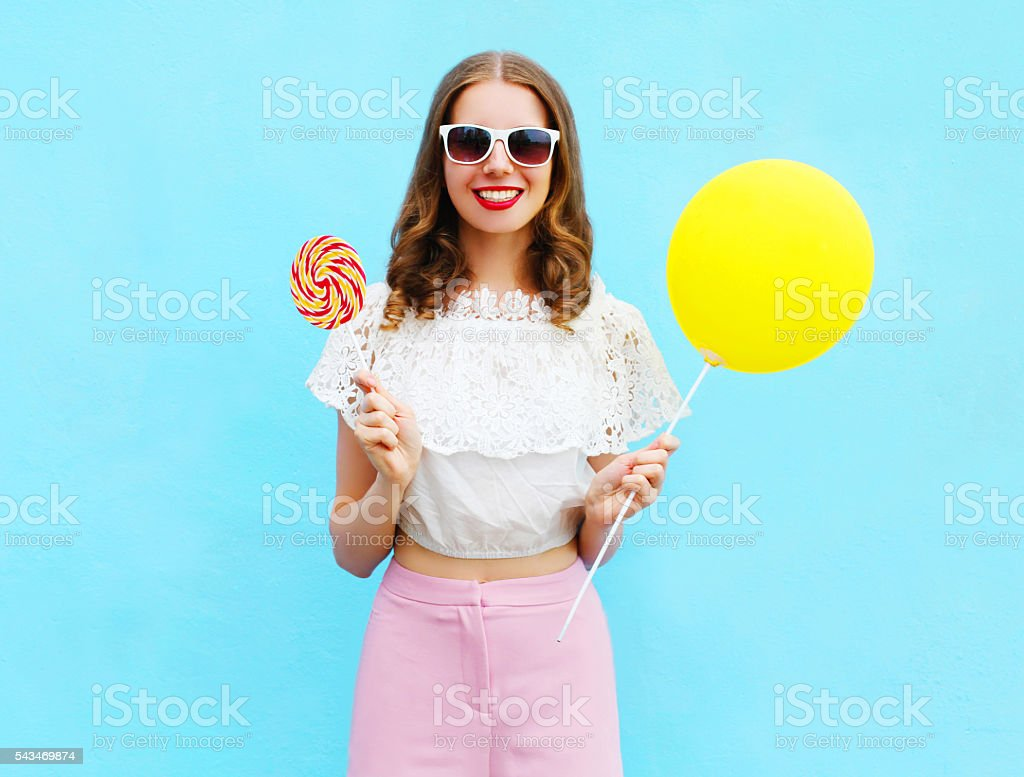 Fashion pretty smiling woman with air balloon and lollipop over stock photo