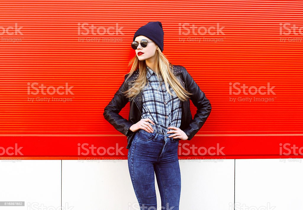 Fashion pretty woman in rock black style posing over red stock photo