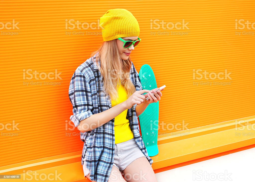 Fashion pretty woman using smartphone with skateboard over colorful stock photo