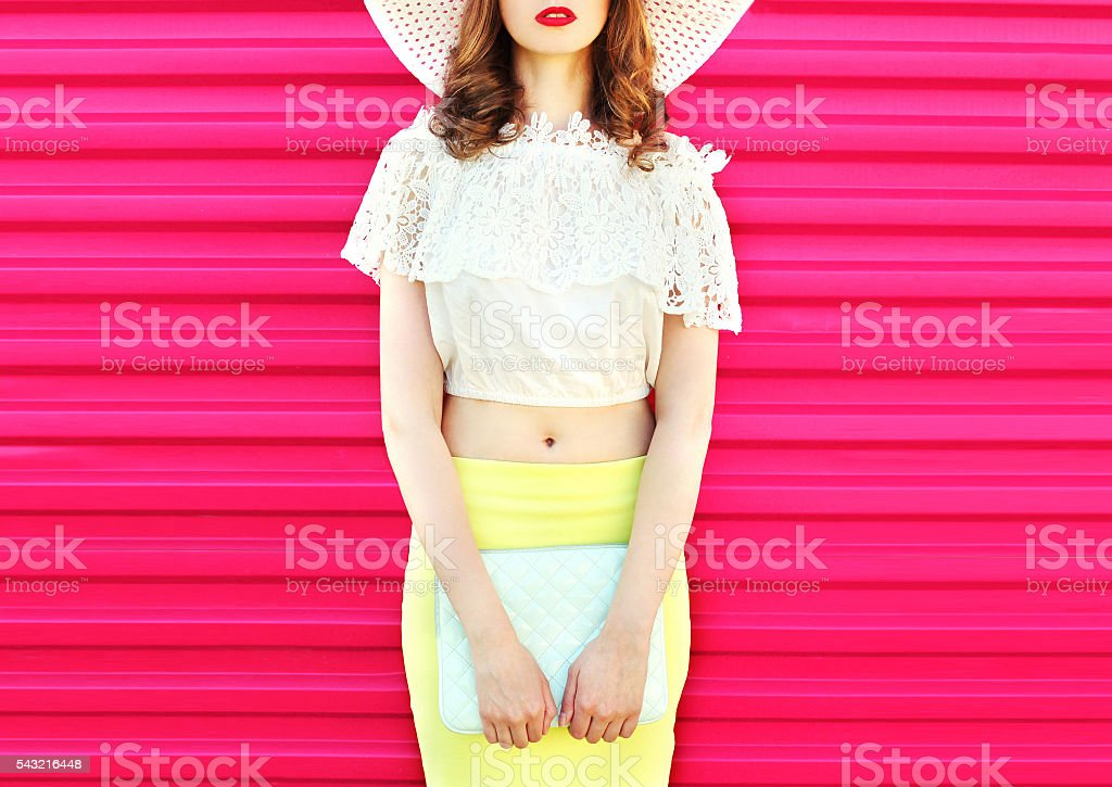 Fashion pretty woman with handbag clutch over colorful pink background stock photo