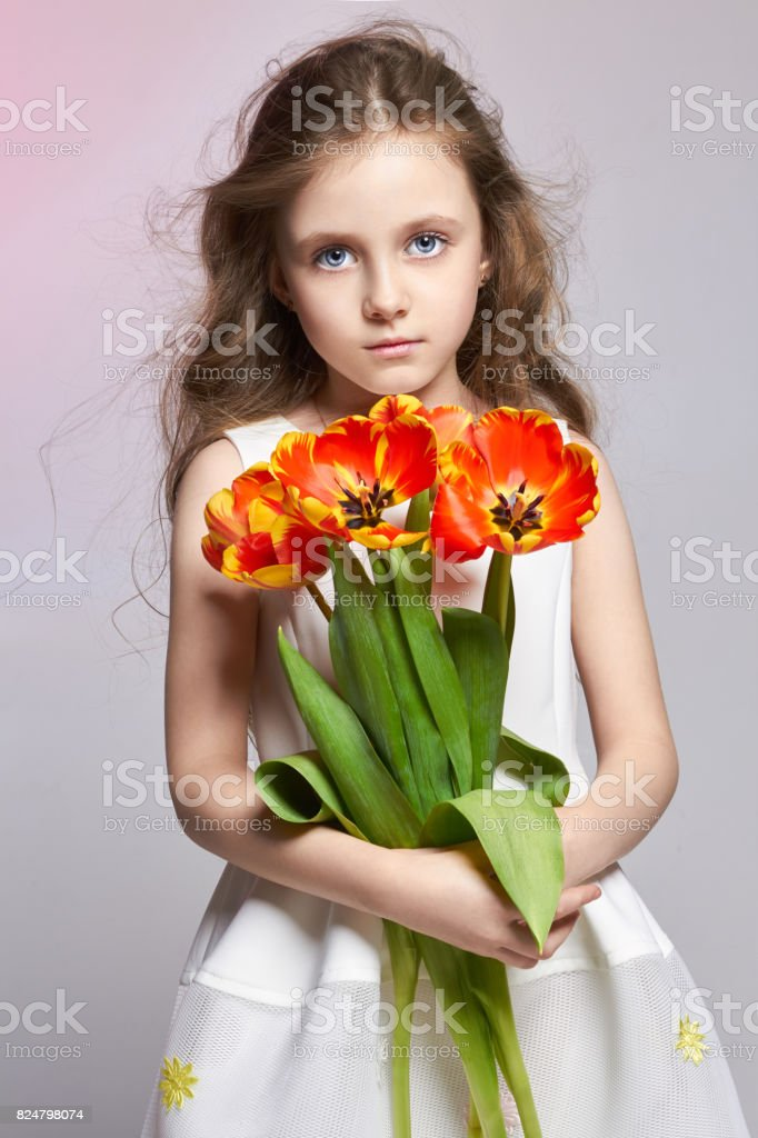 Fashion red-haired girl with tulips in hands. Studio photo on light coloured background. Birthday, holiday, mother's day, first day of school stock photo