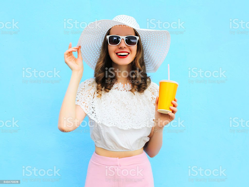 Fashion smiling woman with cup fruit juice over colorful blue stock photo