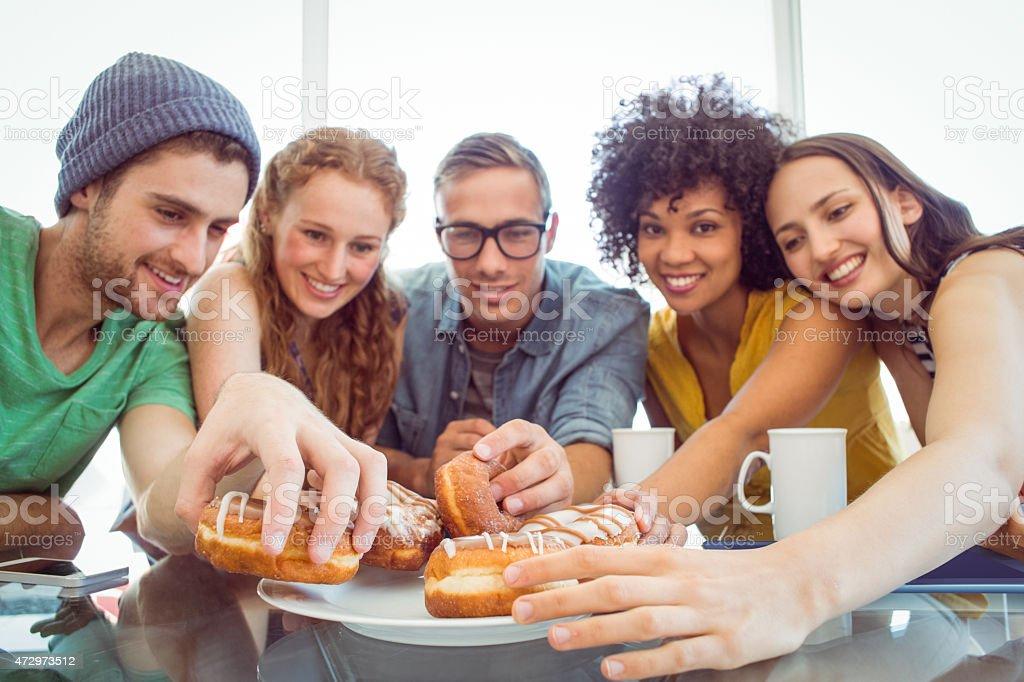 Fashion students eating doughnuts stock photo
