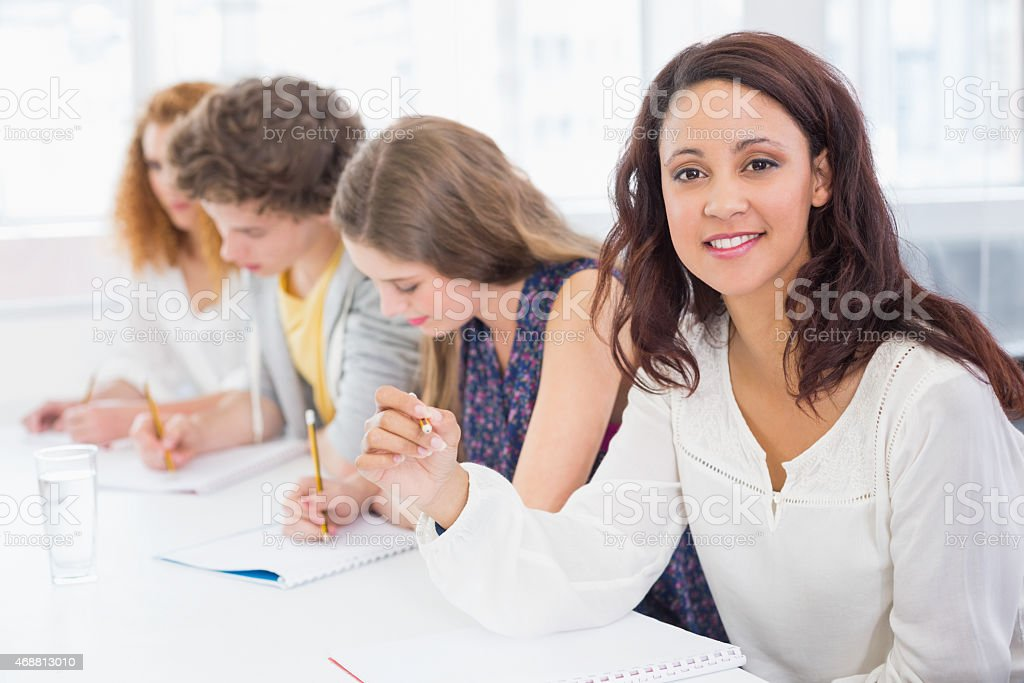 Fashion students smiling at camera in class stock photo