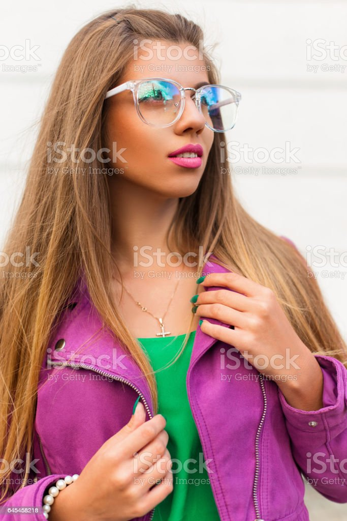 Fashion stylish girl in sunglasses and a bright pink jacket on a white background stock photo