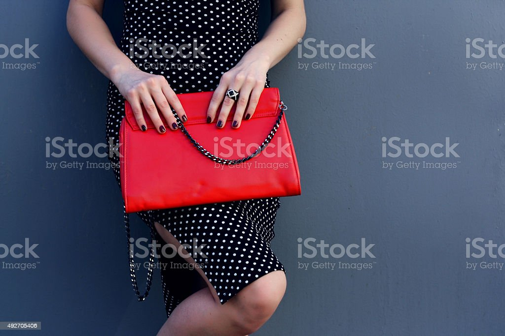 Fashion stylish young woman with red clutch in hand stock photo