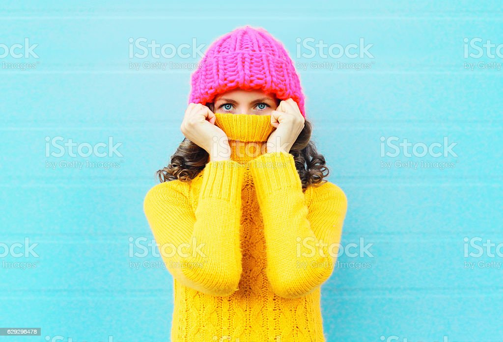 Fashion woman hide face wearing knitted pink hat yellow sweater stock photo