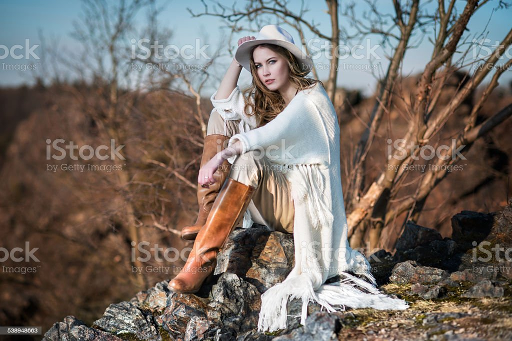 Fashion woman in country style sitting on the canyon rock stock photo