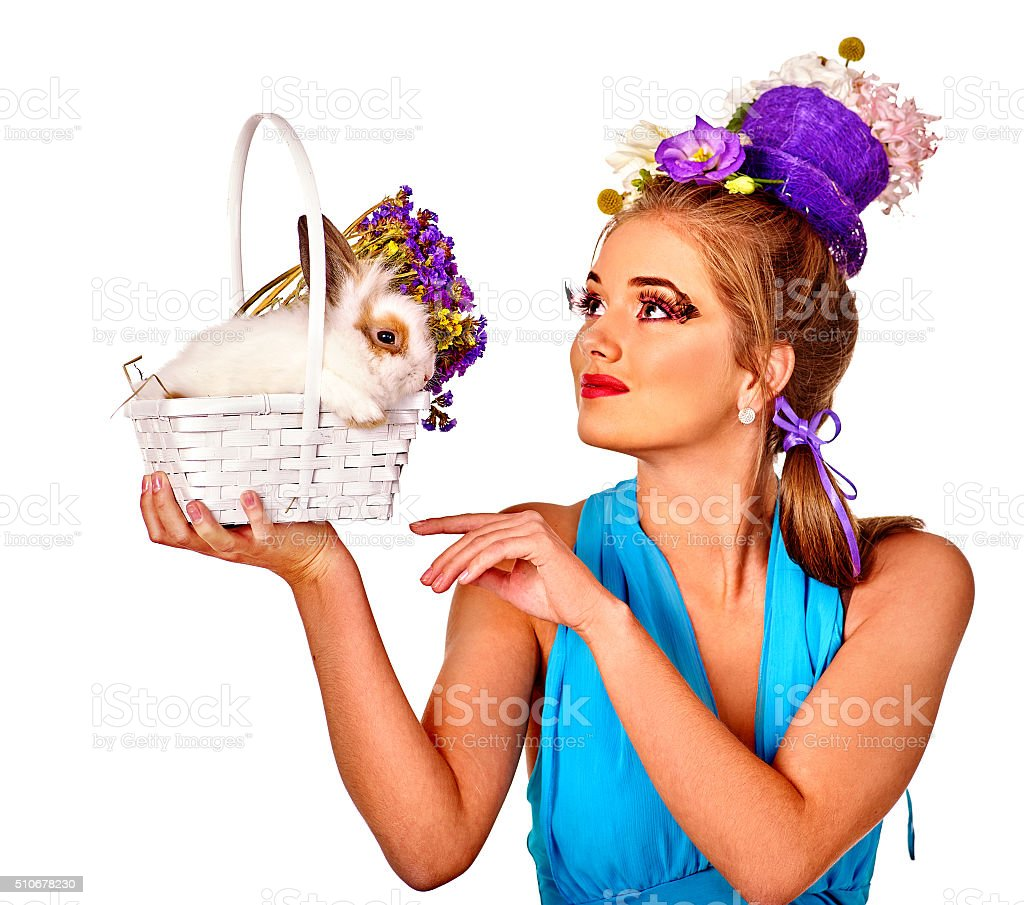 Fashion woman in easter style admires to bunny and flowers stock photo