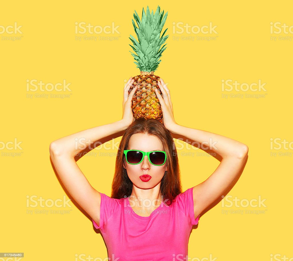 Fashion woman in sunglasses with pineapple on head over yellow stock photo