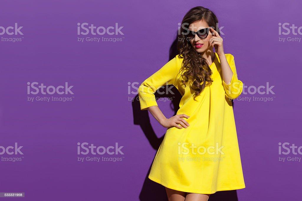 Fashion Woman In Yellow Mini Dress And Sunglasses Looking Away stock photo