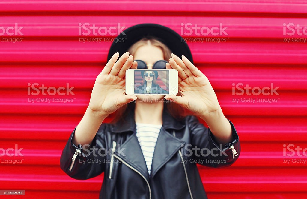 Fashion woman makes self portrait on smartphone over city pink stock photo