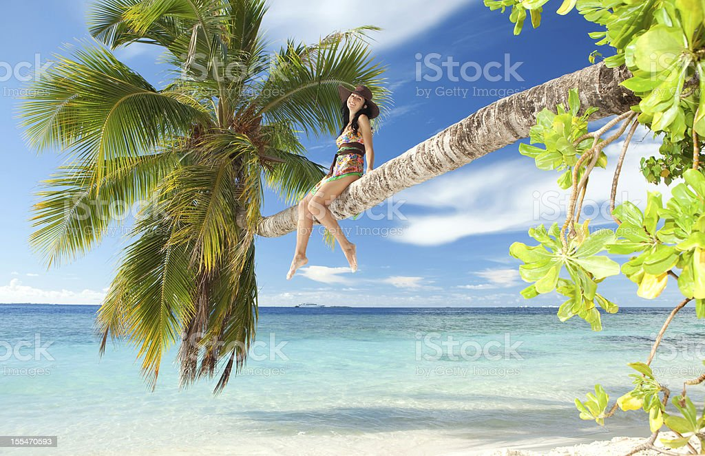 Fashion woman siting upon palm tree on the beach royalty-free stock photo