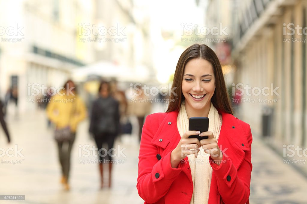 Fashion woman using a smartphone in winter stock photo