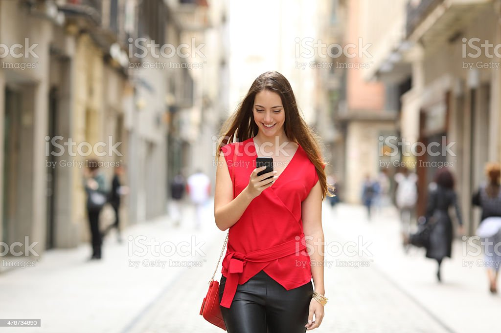 Fashion woman walking and using a smart phone stock photo