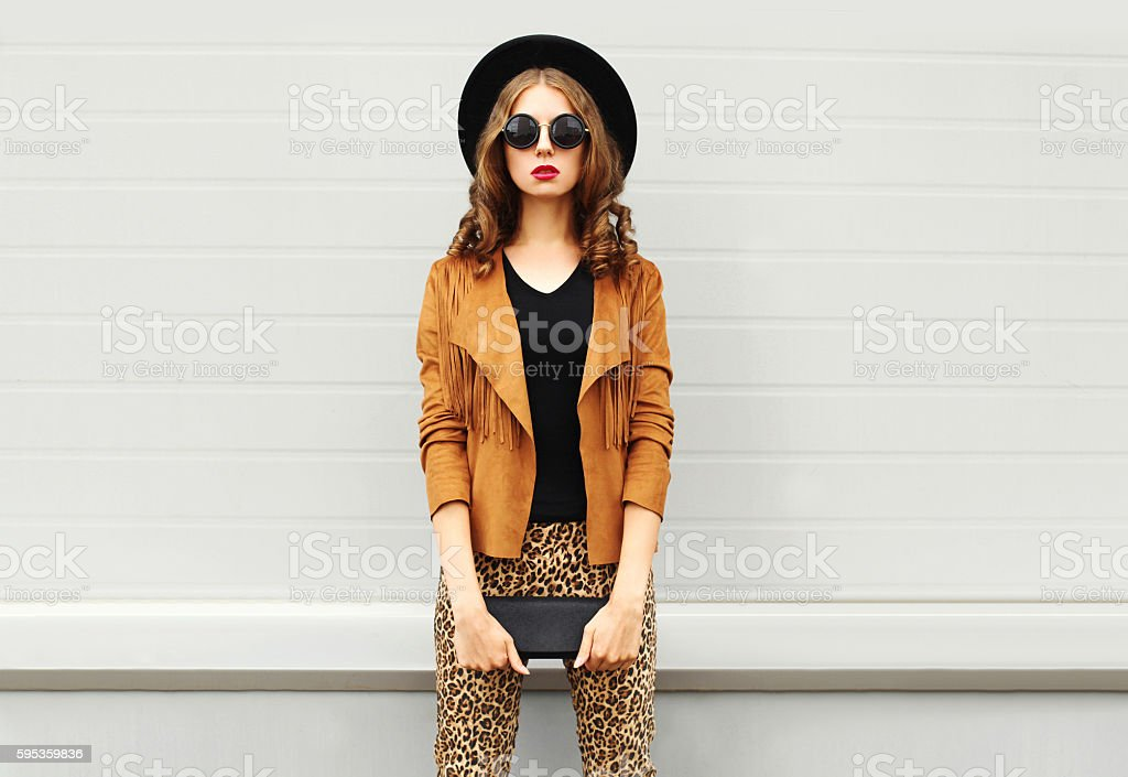 Fashion woman wearing elegant hat, jacket handbag clutch over background stock photo