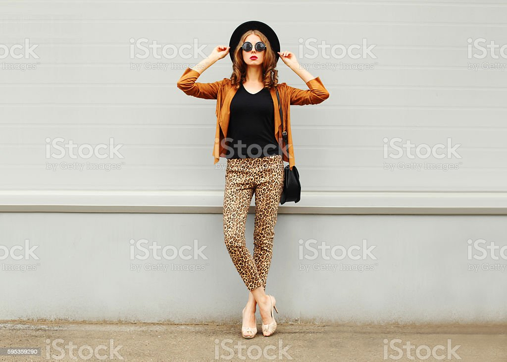 Fashion woman wearing hat, sunglasses, jacket, handbag posing in city stock photo