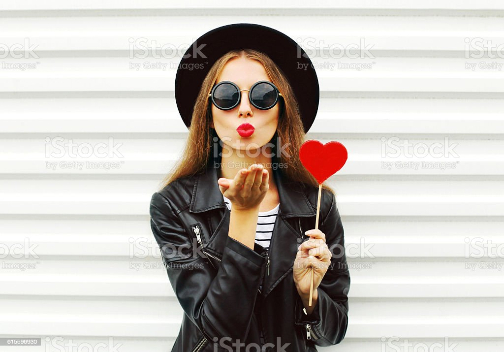 Fashion woman with red lips sends air kiss lollipop heart stock photo