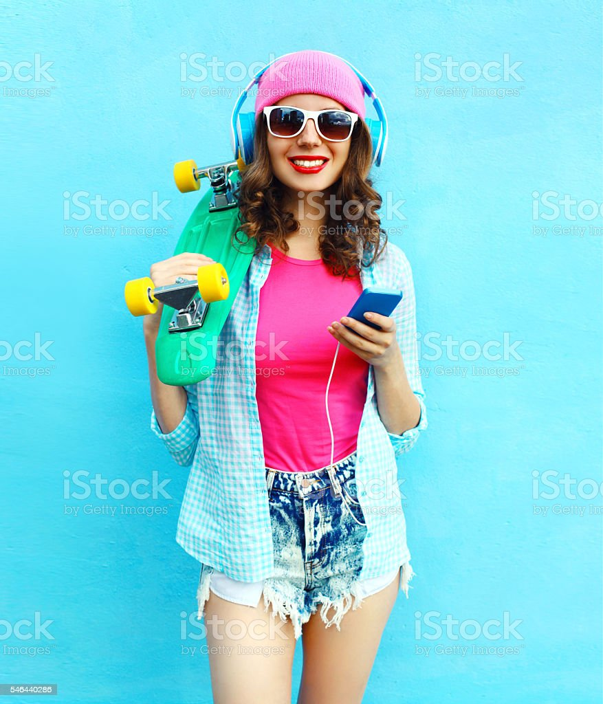 Fashion woman with skateboard headphones listen music in smartphone stock photo