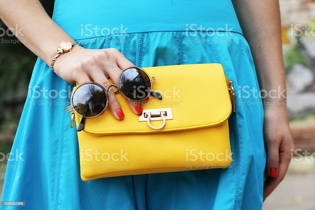 fashion woman with yellow clutch and blue skirt stock photo
