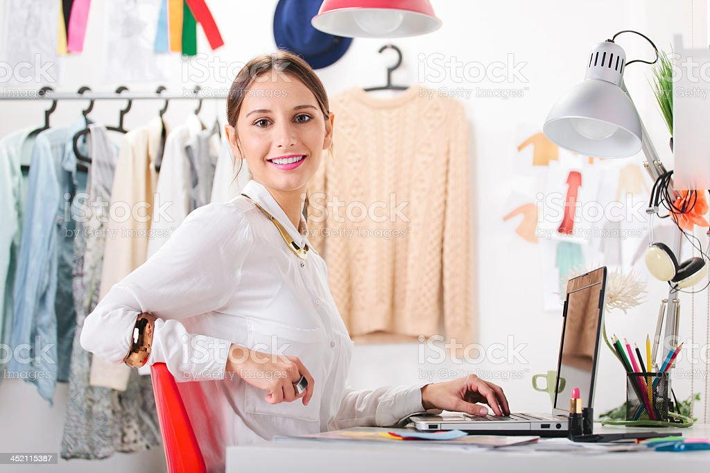 Fashion woman working on laptop in shop stock photo