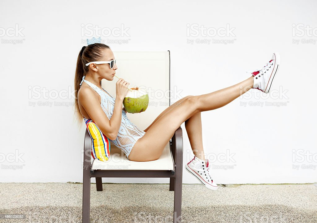 fashion young woman  drinking coconut water and sitting on chair stock photo