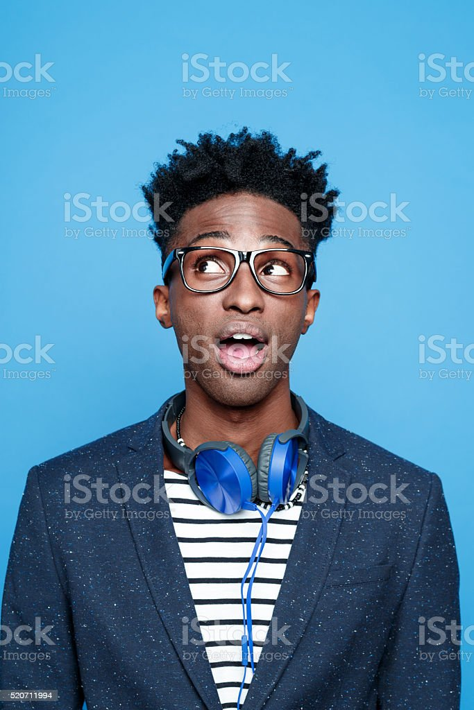 Fashionable afro american young man against blue background stock photo
