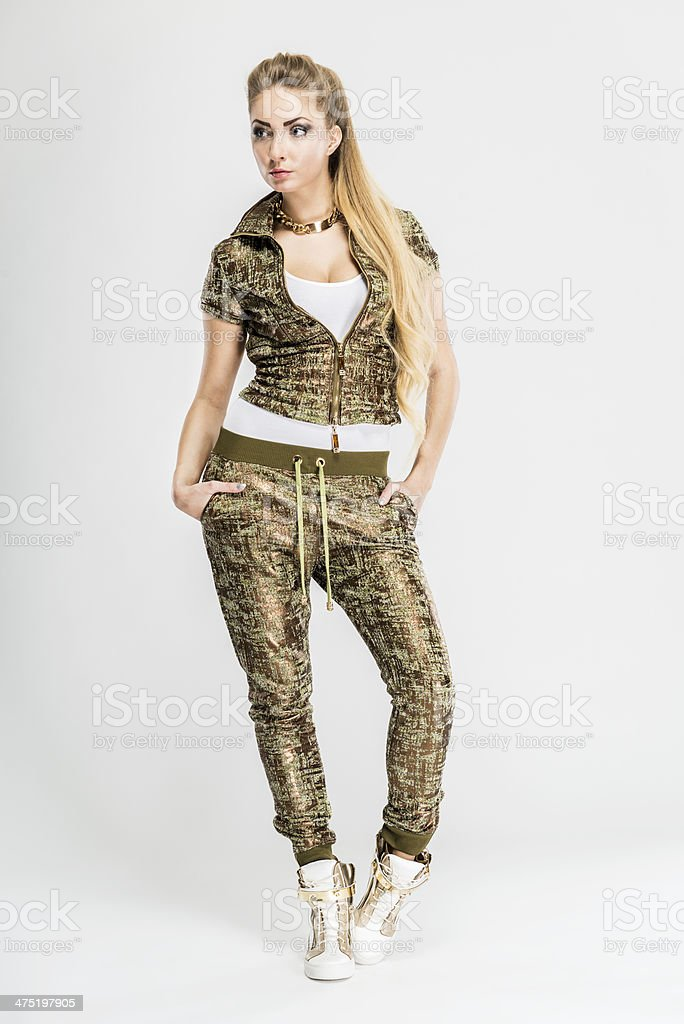 Fashionable Apres-Ski woman's shiny tracksuit in golden color, isolated stock photo