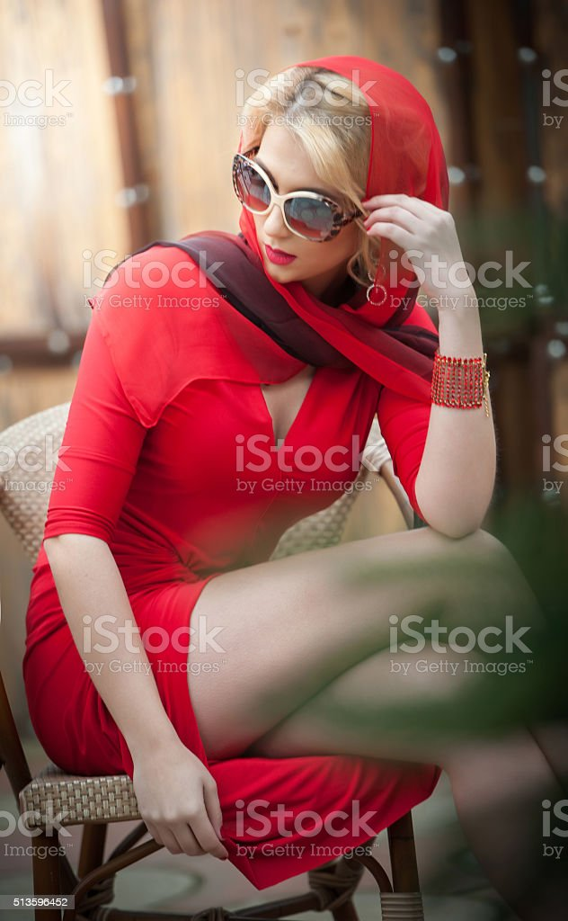 Fashionable attractive lady with red dress and headscarf stock photo