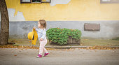 Fashionable baby girl walking with a yellow hat